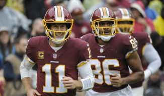 Washington Redskins quarterback Alex Smith (11) smiles as he runs off the filed after wide receiver Jamison Crowder (80) scored a touchdown during the first half of an NFL football game between the Washington Redskins and the Green Bay Packers, Sunday, Sept. 23, 2018 in Landover, Md. (AP Photo/Mark Tenally)