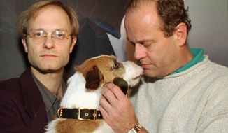 """Actor Kelsey Grammer of the television show, """"Frasier,"""" gets a kiss from the dog, who plays Eddie, as co-star David Hyde Pierce holds Eddie during the opening day of the National Association of Television Program Executives convention Tuesday, Jan. 23, 1996, in Las Vegas. (AP Photo/Lennox McLendon)"""