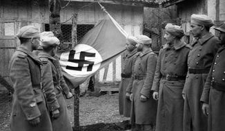 Displaying a Nazi flag seized in combat at the Western Front, these French North African soldiers look over their prize after the encounter on April 4, 1940. (AP Photo)