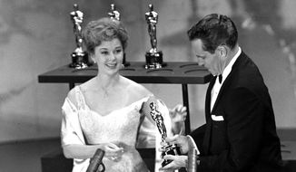 """Susan Hayward presents an Oscar to Charlton Heston, during the annual Academy Awards show in Hollywood, Calif., on April 4, 1960. Heston was awarded best actor for his role in """"Ben-Hur.""""  (AP Photo )"""