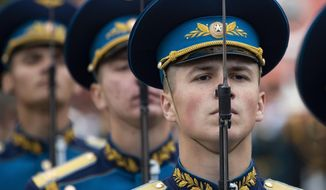 Russians stand during the Victory Day military parade to celebrate 74 years since the victory in WWII in Red Square in Moscow, Russia, Thursday, May 9, 2019. Putin told the annual military Victory Day parade in Red Square that the country will continue to strengthen its armed forces. (AP Photo/Alexander Zemlianichenko)
