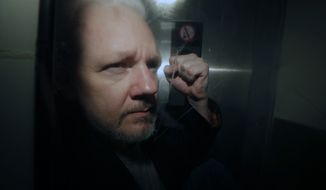 In this May 1, 2019, file photo, WikiLeaks founder Julian Assange puts his fist up as he is taken from court in London. (AP Photo/Matt Dunham, File)