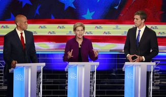 Democratic presidential candidate Sen. Elizabeth Warren, D-Mass., speaks during a Democratic primary debate hosted by NBC News at the Adrienne Arsht Center for the Performing Arts, Wednesday, June 26, 2019, in Miami, as Sen. Cory Booker , D-N.J., and former Texas Rep. Beto O'Rourke, listen. (AP Photo/Wilfredo Lee)