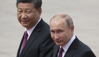 In this June 8, 2018, Russian President Vladimir Putin, right, and Chinese President Xi Jinping walk together during a welcome ceremony outside the Great Hall of the People in Beijing, China. If Donald Trump is serious about his public courtship of Vladimir Putin, he may want to take pointers from one of the Russian leader's longtime suitors: Chinese President Xi Jinping. In this political love triangle, Putin and Xi are tied by strategic need and a rare dose of personal affection, while Trump's effusive display in Helsinki showed him as an earnest admirer of the man leading a country long considered America's adversary. (AP Photo/Alexander Zemlianichenko, File)