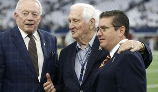 FILE - In this Nov. 24, 2016, file photo, Dallas Cowboys team owner, Jerry Jones, left, Gil Brandt of NFL.Com, center,  and Washington Redskins team owner Daniel Snyder pose for a photo on the field during team warm ups before an NFL football game in Arlington, Texas. Brandt will be inducted into the Pro Football Hall of Fame in Canton, Ohio on Aug. 3, 2019. (AP Photo/Michael Ainsworth, File)