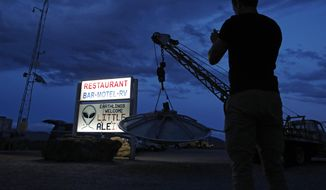 "A man takes a picture of a sign at the Little A'Le'Inn during an event inspired by the ""Storm Area 51"" internet hoax, Thursday, Sept. 19, 2019, in Rachel, Nev. Hundreds have arrived in the desert after a Facebook post inviting people to ""see them aliens"" got widespread attention and gave rise to festivals this week. (AP Photo/John Locher)"