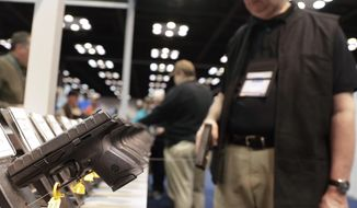 In this April 27, 2019, file photo, a gun enthusiast looks over the display of pistols in the exhibition hall at the National Rifle Association annual meeting in Indianapolis. The number of background checks conducted by federal authorities is on pace to break a record by the end of this year. (AP Photo/Michael Conroy) **FILE**
