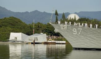 In this Dec. 7, 2016, file photo, sailors on the USS Halsey salute while passing by the USS Arizona Memorial during a moment of silence at Pearl Harbor, Hawaii. (AP Photo/Eugene Tanner, File)