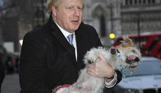 Britain's Prime Minister and Conservative Party leader Boris Johnson holds his dog Dilyn after voting in the general election at Methodist Central Hall, Westminster, London, Thursday Dec. 12, 2019.  Dogs wait outside while their owners go into polling stations to cast their ballot in a general election Thursday Dec. 12, 2019.  U.K. voters are deciding Thursday who they want to resolve the stalemate over Brexit in a parliamentary election widely seen as one of the most decisive in modern times. (AP Photo/Alberto Pezzali)