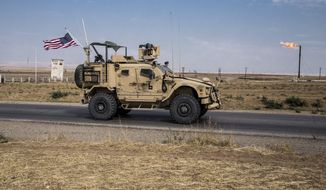 In this Oct. 28, 2019, photo, U.S. forces patrol Syrian oil fields, in eastern Syria. (AP Photo/Baderkhan Ahmad) **FILE**