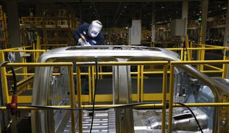 In this Nov. 11, 2014, file photo, Ron Hudgins welds a 2015 Ford F-150 cab at the Dearborn Truck Plant in Dearborn, Mich. (AP Photo/Paul Sancya) ** FILE **