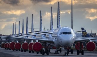 Vueling Airlines planes sit parked in a line at the Seville, Spain airport on Saturday, March 21, 2020, idled due to the COVID-19 coronavirus outbreak. (AP Photo/Miguel Morenatti)