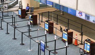 A lone TSA agent sits at a his post with virtually no travelers midday at the B-side security check at Orlando International Airport, Tuesday, April 7, 2020, in Orlando, Fla., as U.S. domestic and international carriers continue to slash flights in response to the coronavirus crisis. (Joe Burbank/Orlando Sentinel via AP)