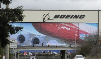 In this March 23, 2020, file photo, cars are driven near Boeing's manufacturing facility in Everett, Wash., north of Seattle. Boeing says it will resume production of its commercial airplanes in phases at its Seattle area facilities next week after suspending operations in March because of the COVID-19 pandemic. (AP Photo/Ted S. Warren, File)