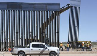 "In this March 24, 2020, file photo, a new section of 30-foot-high ""bollard style wall"" is lifted into place at a construction site south of Yuma, Ariz., near the border between the United States and Mexico. (Randy Hoeft/The Yuma Sun via AP, File)"