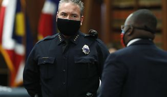 Denver Police Department Chief Paul Pazen, left, wears a face mask while waiting for Denver Mayor Michael Hancock to enter a news conference to explain the city's plan to allow businesses to reopen as the city's stay-at-home order to stem the rise of the new coronavirus expires later this week on Tuesday, May 5, 2020, in Denver. (AP Photo/David Zalubowski)