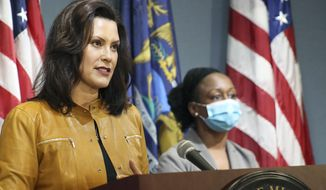 In this photo provided by the Michigan Office of the Governor, Michigan Gov. Gretchen Whitmer addresses the state during a speech in Lansing, Mich., Thursday, May 7, 2020. Whitmer said that auto and other manufacturing workers can return to the job next week, further easing her stay-at-home order while extending it through May 28 because of the coronavirus pandemic. (Michigan Office of the Governor via AP, Pool)