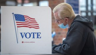 Chuck Schweitzer votes with a mask at a voting booth during Nebraska primary election in Lincoln, Neb., Tuesday, May 12, 2020. (Justin Wan/Lincoln Journal Star via AP)  **FILE**