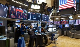 In this Monday, March 16, 2020, file photo, traders work on the floor of the New York Stock Exchange near the end of the trading day. The New York Stock Exchange will partially reopen its trading floor, Tuesday, May 26, after closing it in late March due to the coronavirus pandemic. (AP Photo/Craig Ruttle, File)