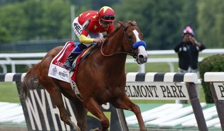 In this June 9, 2018, file photo, Justify,  jockey Mike Smith up, crosses the finish line to win the 150th running of the Belmont Stakes horse race and the Triple Crown at Belmont Park in Elmont, N.Y. The Belmont Stakes will be run June 20, 2020, without fans and serve as the opening leg of horse racing's Triple Crown for the first time in the sport's history. The New York Racing Association on Tuesday, May 19, 2020, unveiled the rescheduled date for the Belmont, which will also be contested at a shorter distance than usual. This is the first time the Belmont will lead off the Triple Crown ahead of the Kentucky Derby and Preakness.(AP Photo/Peter Morgan) ** FILE **