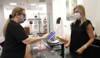 In this Wednesday, May 13, 2020, photo, Monique Kursar, left, completes a purchase with Amy Witt, owner of the Velvet Window, in Dallas. Small businesses are navigating a new way to work with customers amid concerns of the spread of the coronavirus. (AP Photo/LM Otero)