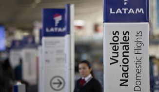 In this July 25, 2016, file photo, an agent of LATAM airlines stands by the counters at the airport in Santiago, Chile. The South American carrier said Tuesday, May 26, 2020, that it is seeking Chapter 11 bankruptcy protection as it grapples with the sharp downturn in air travel sparked by the coronavirus pandemic. (AP Photo/Esteban Felix, File)