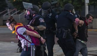 Protesters are restrained by police during a rally in downtown Indianapolis on Saturday, May 30, 2020. Protests were held in U.S. cities over the death of George Floyd, a black man who died after being restrained by Minneapolis police officers on May 25.  (Mykal McEldowney/The Indianapolis Star via AP) **FILE**