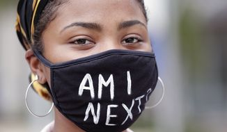 A demonstrator with a message on her mask stands quietly during a peaceful demonstration to protesting the death of George Floyd Monday, June 8, 2020, in Orlando, Fla. Floyd died while being detained by police in Minneapolis on May 25. (AP Photo/John Raoux)
