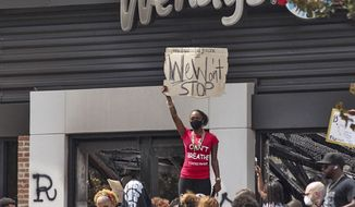 People hold a rally at Wendy's on University Avenue in Atlanta on Sunday, June 14, 2020. Rayshard Brooks died after a confrontation with police officers at the fast-food restaurant in Atlanta on Friday. (Steve Schaefer/Atlanta Journal-Constitution via AP)