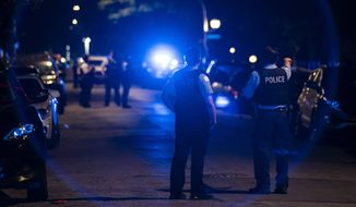 Chicago police officers investigate the scene of a shooting in Chicago on Sunday, July 5, 2020. At least a dozen people, including a 7-year-old girl at a family party and a teenage boy, were killed in Chicago over the Fourth of July weekend, police said. Scores of people were shot and wounded. (Ashlee Rezin Garcia/Chicago Sun-Times via AP)