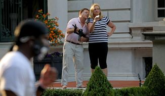 In this June 28, 2020, file photo, armed homeowners Mark and Patricia McCloskey, standing in front their house along Portland Place confront protesters marching to St. Louis Mayor Lyda Krewson's house in the Central West End of St. Louis. (Laurie Skrivan/St. Louis Post-Dispatch via AP) ** FILE **