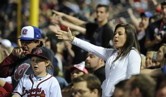 """In this May 2, 2014, file photo, Atlanta Braves fans do the tomahawk chop during the ninth inning of a baseball game with the San Francisco Giants, in Atlanta. The Atlanta Braves say they have no plans to follow the lead of the NFL's Washington Redskins and change their team name. The team said in a letter to season ticket holders they are examining the fan experience, including the tomahawk chop chant, and have formed a """"cultural working relationship"""" with the Eastern Band of the Cherokees in North Carolina. (AP Photo/David Tulis, File)"""