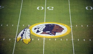In this Aug. 28, 2009 file photo, the Washington Redskins logo is shown on the field before the start of a preseason NFL football game against the New England Patriots in Landover, Md.  The Washington NFL franchise announced Monday that it will drop the Redskins name and Indian head logo immediately, bowing to decades of criticism that they are offensive to Native Americans.  (AP Photo/Nick Wass, File)  **FILE**