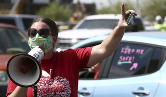 In this file photo from July 15, 2020, local teacher Lisa Vaaler joins other teachers as they hold a #Return2SchoolSafely Motor March protest in Phoenix. At that protest, several Arizona teachers voiced fears about returning to school in a state that continues to be ravaged by the coronavirus. (AP Photo/Ross D. Franklin)  ** FILE **