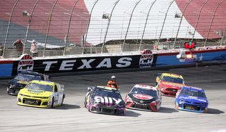 A NASCAR official checks drivers as the race was red flagged for over 11 minutes due to an 11-car incident  during a NASCAR Cup Series auto race at Texas Motor Speedway in Fort Worth, Texas, Sunday, July 19, 2020. (AP Photo/Ray Carlin) **FILE**