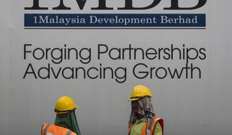 In this May 14, 2015, file photo, construction workers chat in front of a billboard for state investment fund 1 Malaysia Development Berhad (1MDB) at the fund's flagship Tun Razak Exchange development in Kuala Lumpur, Malaysia. Goldman Sachs reaches a $3.9 billion settlement with Malaysia over scandal-plagued 1MDB sovereign wealth fund. (AP Photo/Joshua Paul, File)