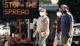 Pedestrians wear masks as they walk in front of a sign reminding the public to take steps to stop the spread of coronavirus, Thursday, July 23, 2020, in Glendale, Calif. (AP Photo/Chris Pizzello) ** FILE **