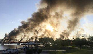 Smoke fills the sky at the scene of a train derailment in Tempe, Ariz., on Wednesday, July 29, 2020. Officials say a freight train traveling on a bridge that spans a lake in the Phoenix suburb derailed and set the bridge ablaze and partially collapsing the structure.  There were no immediate reports of any leaks. (Daniel Coronado via AP)