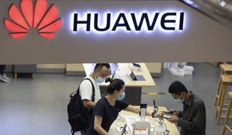 In this Wednesday, July 15, 2020, file photo, visitors look at the latest products at a Huawei store in Beijing. (AP Photo/Ng Han Guan, file)