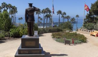 Former San Clemente Mayor Wayne Eggleston lowers the U.S. flag to half-staff at Park Semper Fi in San Clemente, Calif., on Friday, July 31, 2020. Officials say a military seafaring assault vehicle with 15 Marines and a Navy sailor aboard sank off the coast of Southern California, leaving one of the Marines dead and eight missing. A Marine Corps spokesman says they were traveling in the amphibious assault vehicle from the shores of San Clemente Island to a Navy ship Thursday evening when they reported that the vehicle was taking on water. (Paul Bersebach/The Orange County Register via AP)