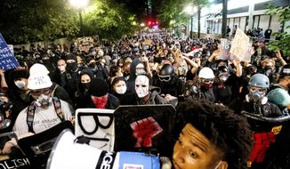 Black Lives Matter protesters march through Portland, Ore. after rallying at the Mark O. Hatfield United States Courthouse on Sunday, Aug. 2, 2020. Following an agreement between Democratic Gov. Kate Brown and the Trump administration to reduce federal officers in the city, nightly protests remained largely peaceful without major confrontations between demonstrators and officers. (AP Photo/Noah Berger) **FILE**