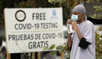 FILE - In this July 22, 2020, file photo, a man takes a coronavirus test at a mobile site at the Charles Drew University of Medicine and Science, in Los Angeles. California has stopped updating a list of counties facing more restrictions on businesses and schools after a problem in the state's coronavirus testing database has led to an undercount. (AP Photo/Marcio Jose Sanchez, File)
