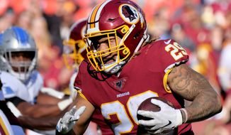 In this Nov. 24, 2019, file photo, Washington Redskins running back Derrius Guice (29) runs the ball during an NFL football game against the Detroit Lions in Landover, Md. The Washington Football Team has released Guice after he was charged in a domestic violence incident. (AP Photo/Mark Tenally) ** FILE **