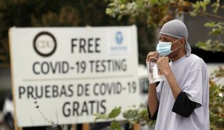 In this July 22, 2020, file photo, a man takes a coronavirus test at a mobile site at the Charles Drew University of Medicine and Science, in Los Angeles. (AP Photo/Marcio Jose Sanchez, File)