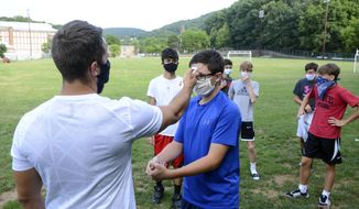 """Head coach Zachary Reichert, left, takes Nicholas Giuffre's temperature prior to the start of Pottsville's boys' soccer practice at Alumni Field in Pottsville, Pa., Thursday, Aug. 6, 2020. During a press conference Thursday, Gov. Tom Wolf recommended that no sports take place until January 1, 2021. Previously, state guidelines posted to the Governor's Office website stated that """"the decision to resume sports-related activities, including conditioning, practices and games, is the discretion of a school entity's governing body."""" Games, as also stated on the Governor's Office website, would be limited to players, coaches, officials, and staff. (Lindsey Shuey/Republican-Herald via AP)"""