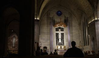 Parishioners sit apart from each other as they practiced social distancing during live streamed Eucharistic Adoration service at Saint Ann Catholic Church in Washington, Sunday night, March 29, 2020. The Archdiocese of Washington has temporarily halted all public Masses and gatherings in an effort to contain the spread of the coronavirus. (AP Photo/Carolyn Kaster)  **FILE**