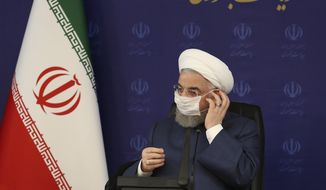 In this July 18, 2020, file photo, released by the official website of the office of the Iranian Presidency, President Hassan Rouhani adjusts his face mask in a meeting of the national headquarters of the fight against the COVID-19, in Tehran, Iran. (Iranian Presidency Office via AP, File)