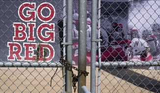 Gates leading into Memorial Stadium are padlocked, in Lincoln, Neb., Wednesday, Aug. 12, 2020. The Big Ten won't play football this fall because of concerns about COVID-19, becoming the first of college sports' power conferences to yield to the pandemic. The move was announced Tuesday. (AP Photo/Nati Harnik)  **FILE**