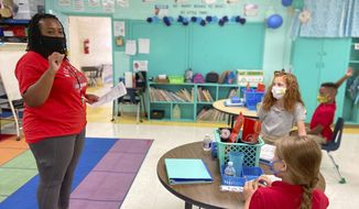 Fourth-grade teacher Krileshia Boyd speaks to her students at Northeast Lauderdale Elementary School in Lauderdale County, Miss., Monday, Aug. 10, 2020. Schools are reopening this week under new guidelines after being closed in March as the COVID-19 pandemic spread. School staff and students are both required to wear masks under an order signed by Gov. Tate Reeves last week. (Bill Graham/The Meridian Star via AP)