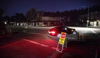 In this Oct. 10, 2019, file photo a car drives through a darkened Montclair Village as Pacific Gas & Electric power shutdowns continue in Oakland, Calif. Pacific Gas and Electric promised regulators Thursday, Aug. 13, 2020, that it has learned from its mishandling of deliberate blackouts and won't disrupt as many people's lives during the pandemic this year, when the utility expects to rely on outages to prevent its outdated grid from starting deadly fires. (AP Photo/Noah Berger, File)